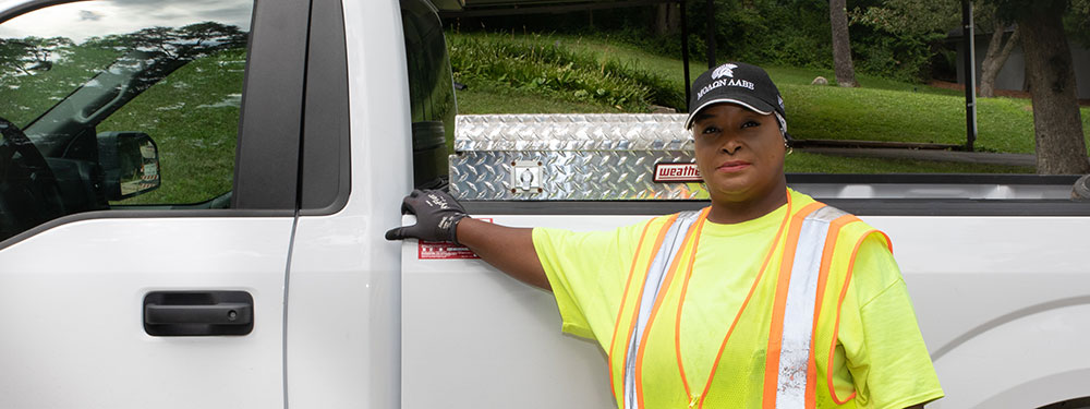 A woman standing by a truck in her work uniform.